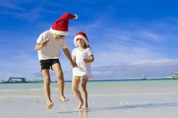 portrait of 2 kids in santa hats
