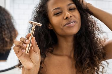 black female model holding rose gold razor