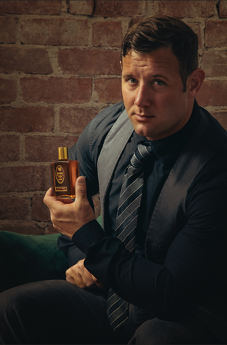young male model holding bottle of aftershave cologne