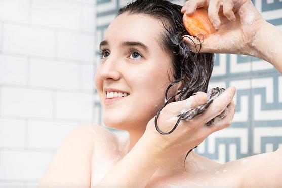 white female model using shampoo bar in shower