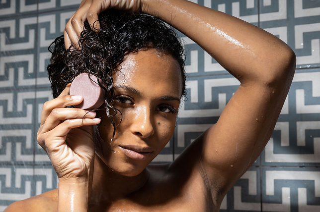 african american model using conditioner bar on hair in shower