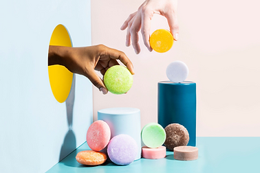 pastel product photography of hand modeling shampoo and conditioner bars