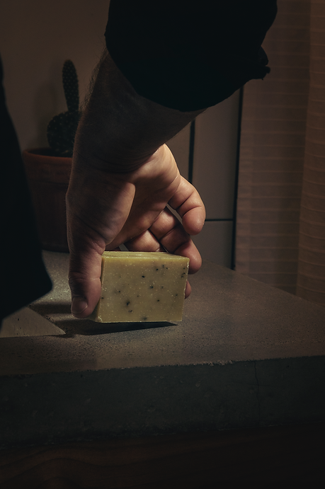 male hand picking up soap bar in masculine bathroom