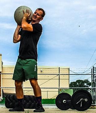 Coach Corey lifting a stone