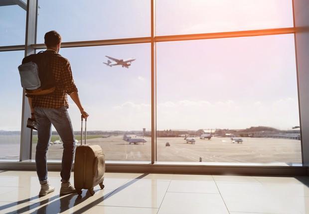 jovem em aeroporto olhando a janela