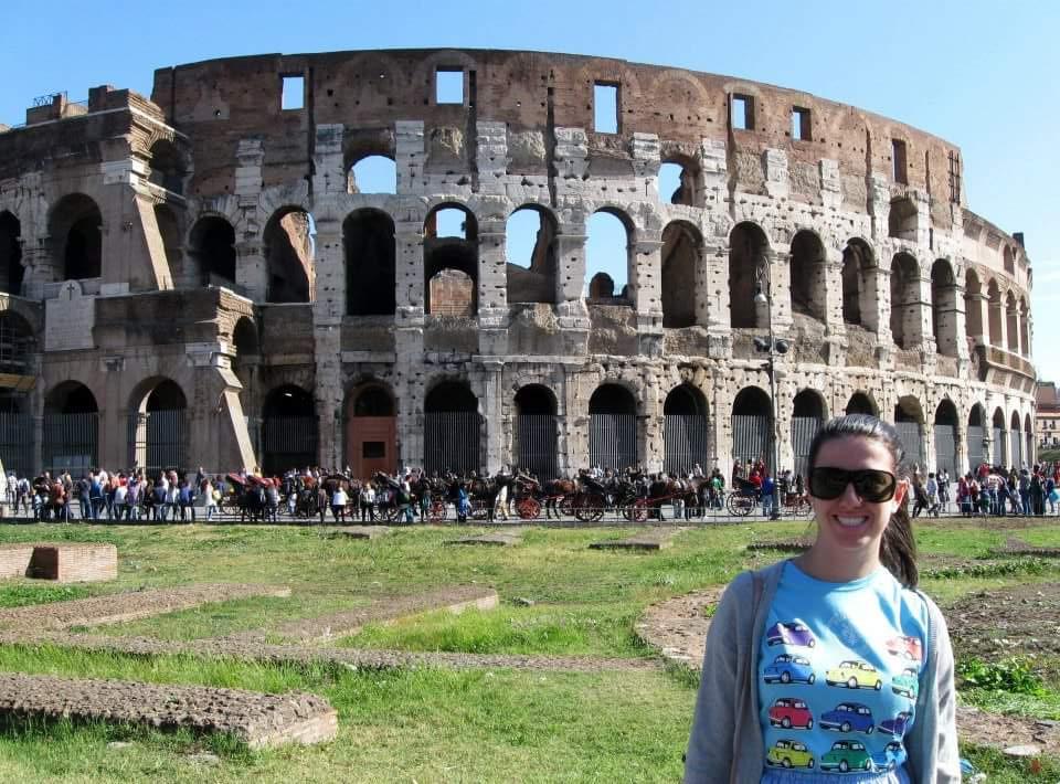 Imagem do Coliseu, com uma menina sorrindo em frente