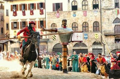cena de uma luta medieval, onde um cavaleiro tenta acertar um boneco com sua lanca
