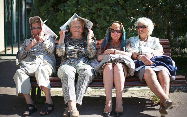 Idosas rindo sentadas em banco na praça