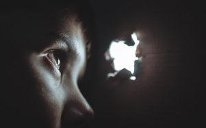 Imagem de uma criança em um ambiente escuro, onde a única fonte de luz é um buraco pelo qual a criança espia