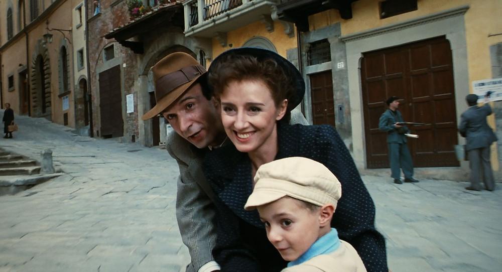 cena do filme a vida e bela, mostra um homem, uma mulher e uma crianca em uma bicicleta