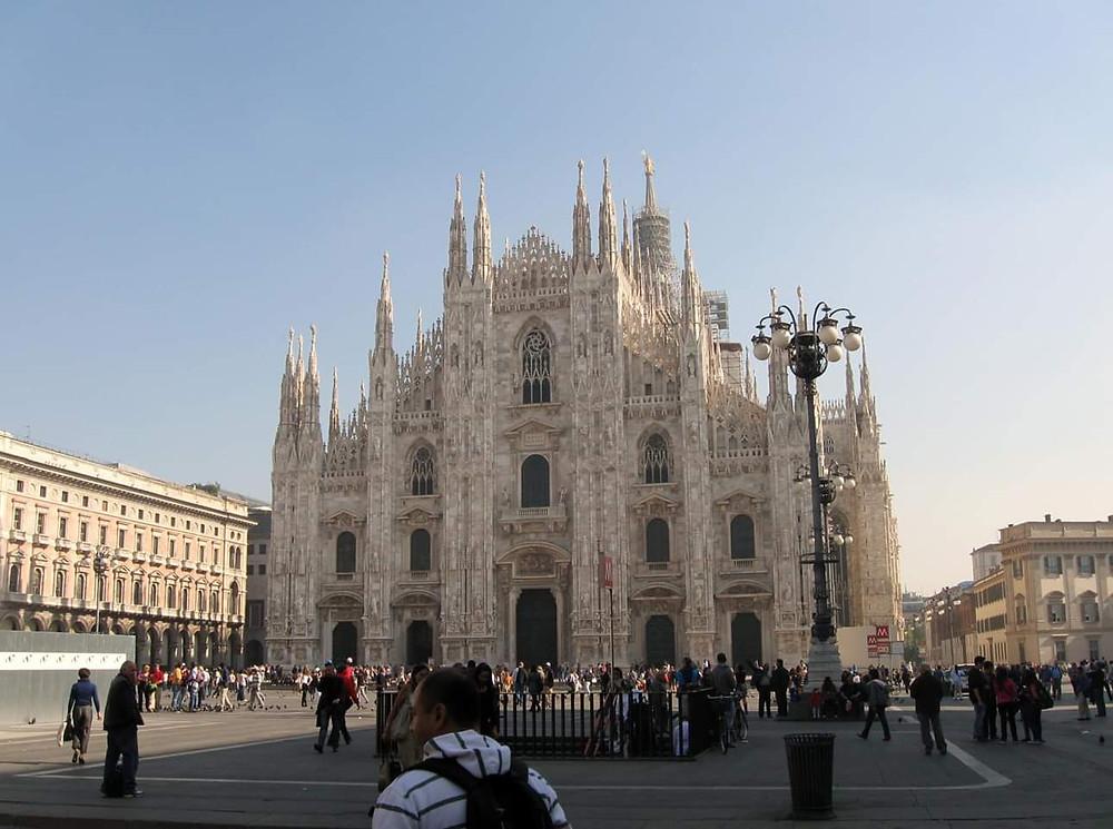 Duomo di Milano que mostra a catedral, a praça em frente e turistas