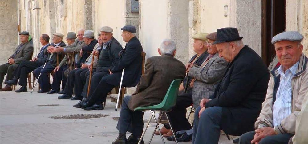 Idosos conversando sentados em cadeiras na praça