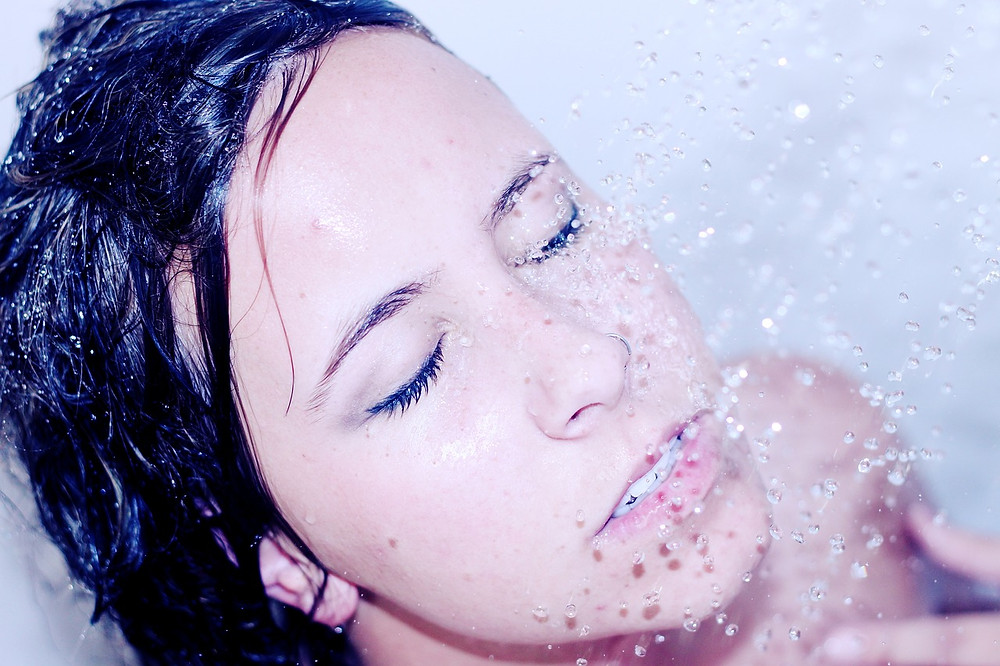 Image of a brunette woman with her eyes closed in the shower with water falling on her face