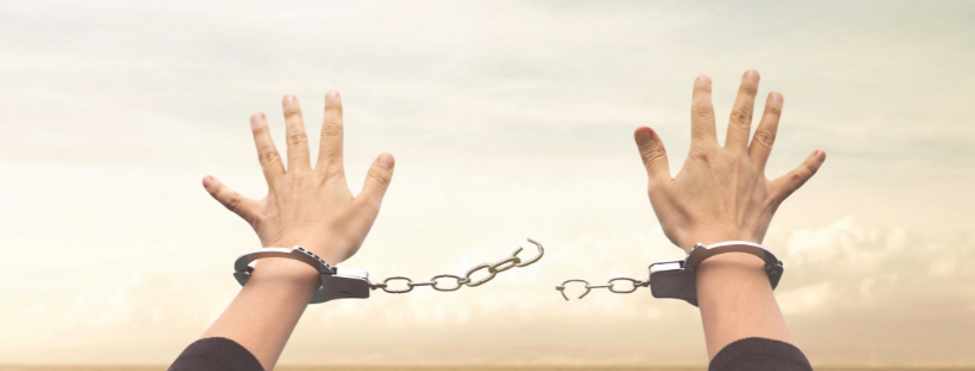 hands in handcuffs, breaking free with blue sky in the background