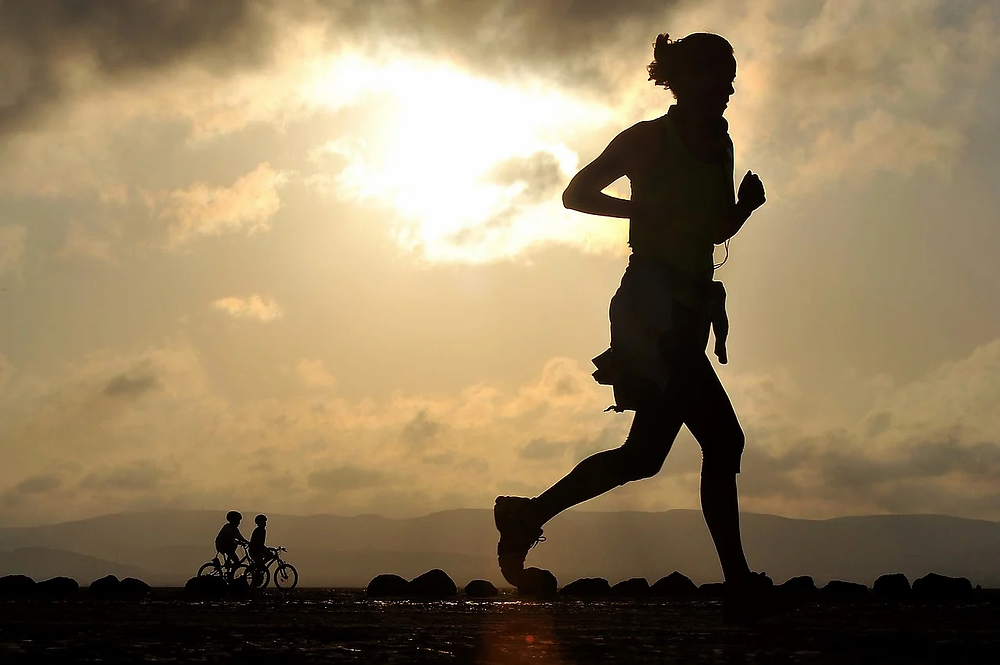 Silhouette of a woman running with the sun and clouds in the background