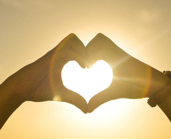 Picture of two peoples hands coking together to make a heart shape in front of the sun.