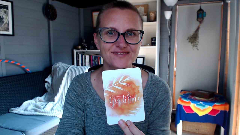Nici is sitting in her office, smiling holding up a card that says Gratitude in white swirly writing with orange watercolour type blot behind the words.