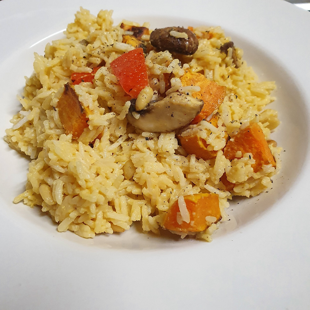 White bowl full of creamy squash rice with roasted sweet potato, mushrooms and red peppers