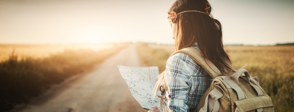 A woman with a backpack consulting a map, with an open road and fields ahead of her