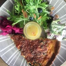 Hausgemachter Quiche mit Lachs und Spinat dazu Salate und Haus Sauce