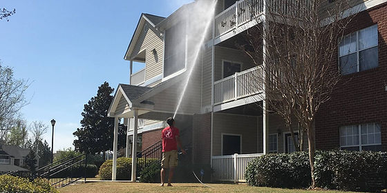 Pressure Washer standing on ground spraying water and soap on a three story apartment building