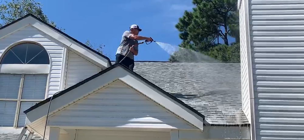 Man soft washing asphalt shingle roof