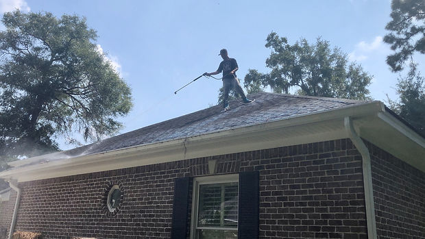 A pressure washer standing on roof softwashing black mold off this Savannah home.