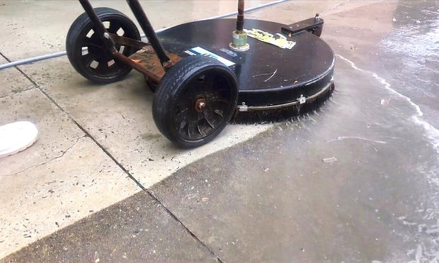 A pressure washing surface cleaner washing concrete in Savannah, Georgia