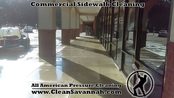 Pressure washing a concrete sidewalk at a shopping center in Savannah