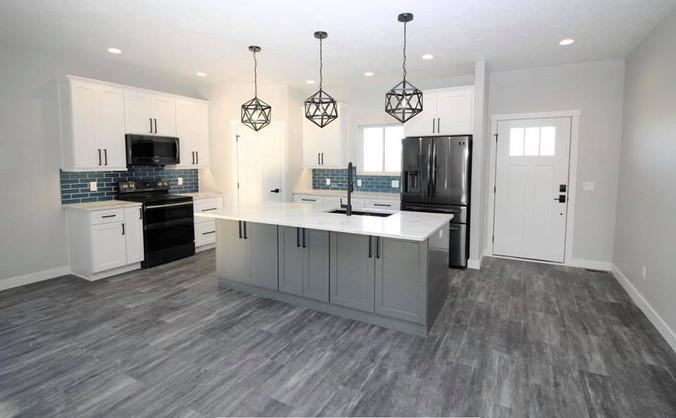 US Cabinet Depot: Shaker White & Shaker Gray Cabinetry. MSI Quartz: Carrara Luccia. Eternity Flooring: Legacy Slate WPC