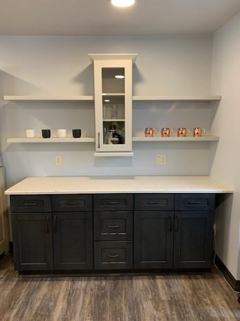 US Cabinet Depot: Shaker Cinder & Shaker Dove (including floating shelves). MSI Quartz: Carrara Mist. Eternity Flooring: Ashbury WPC