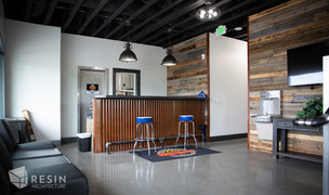 Recepting area with barn wood wall cladding and corrugated steel wrapping reception desk inside Total Trailer Co.