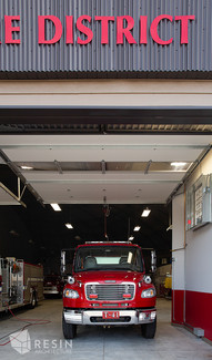View of a firetruck inside with the exterior bay doors open at South Summit Fire Station.