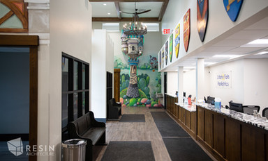 Reception area of Idaho Falls Pediatrics complete with murals, chandeliers, and shields.