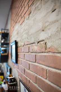 Detail shot of the distressed brick accent wall inside Elite Auto Sales in Idaho Falls.