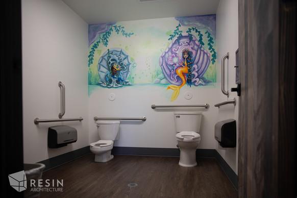 Custom bathroom at Idaho Falls Pediatrics with dragon mural and small and large toilets.