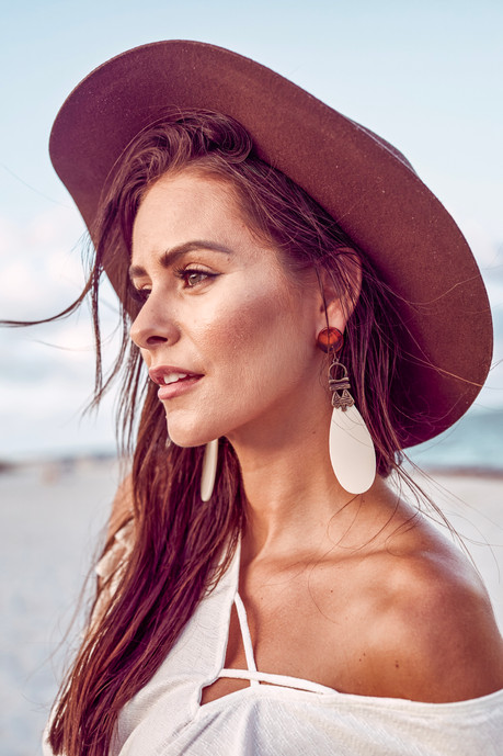 brunette woman looking to the left wearing a brown boho hat and earings made of feather with the sunset touching her face