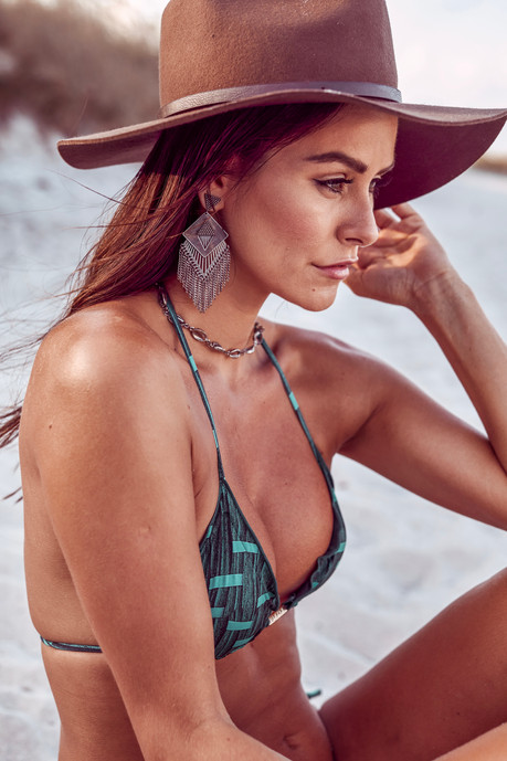 brunette woman looking to the right, wearing a brown boho hat, a dark green bikini top and metal earing