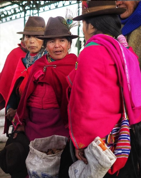 An exchange between colorfully dressed women in an Ecuadorian market