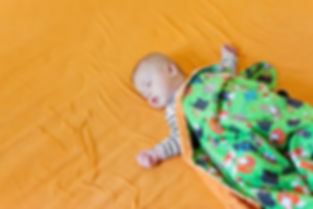 Cute baby sleeping on big bed covered wi