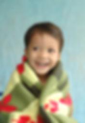 Cheerful little boy in blanket.jpg