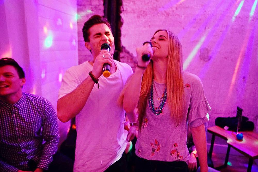 Man and women singing karaoke