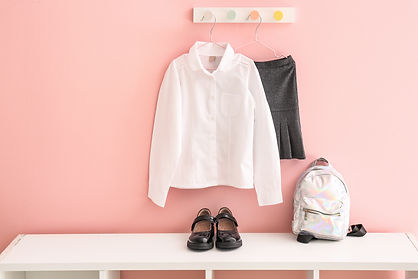 Stylish school uniform with backpack and shoes in room.jpg