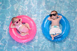 Two month old twin baby sister and brother sleeping on tiny, inflatable, pink and blue swi