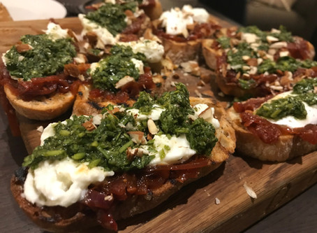 Crostini with harissa red onion jam, burrata and salsa verde