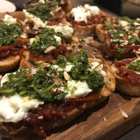 Crostini with harissa red onion jam, burrata and salsa verde