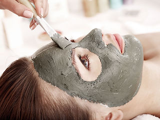 A relaxing mud mask is being applied to the Clients face