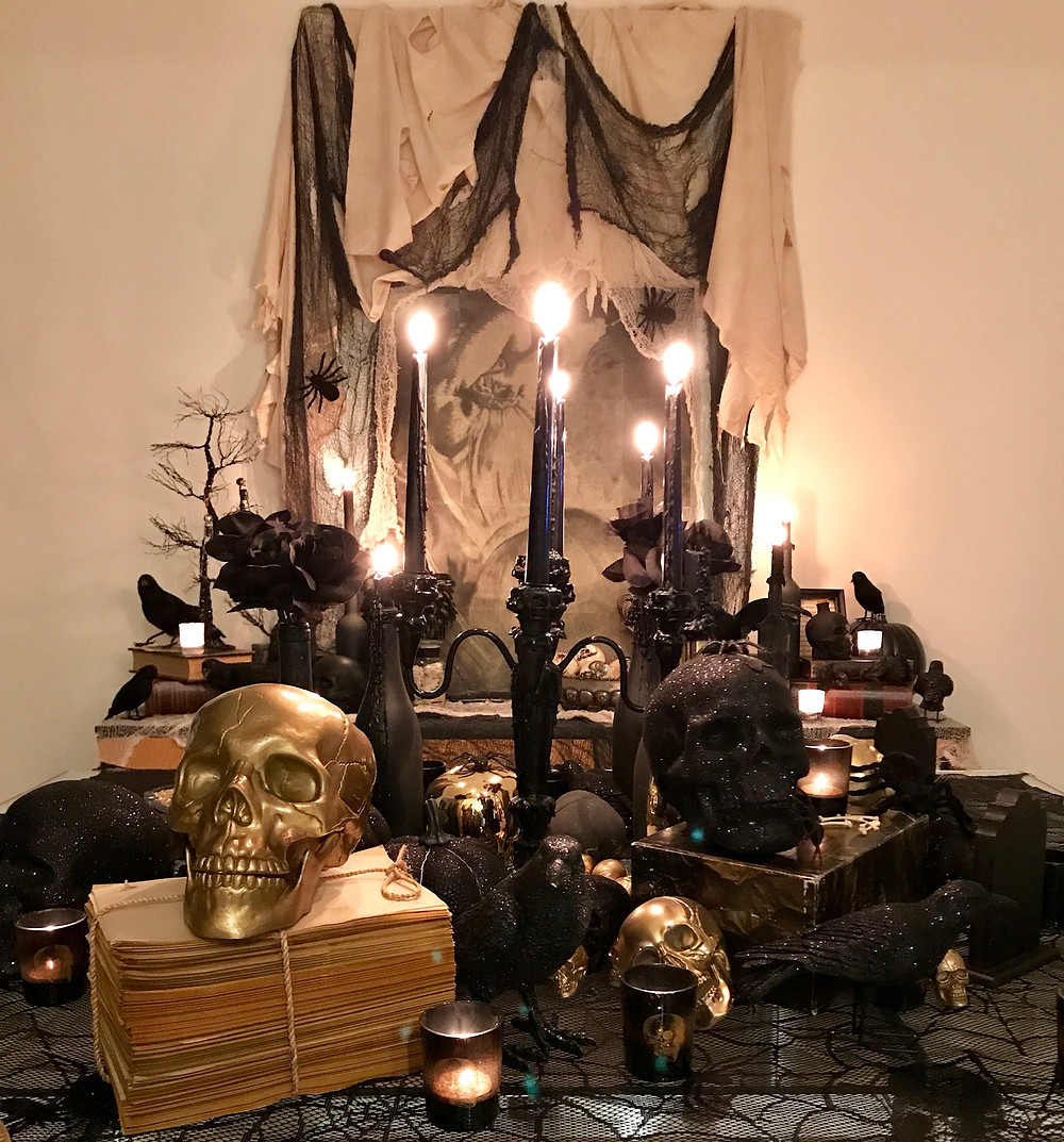 black and gold layered tablescape for halloween. black drip candles with clothes and skeletons. Interior design for houston