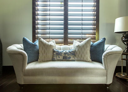 Master bedroom sitting area, loveseat with neutral fabric, pillows and pops of blue pillows