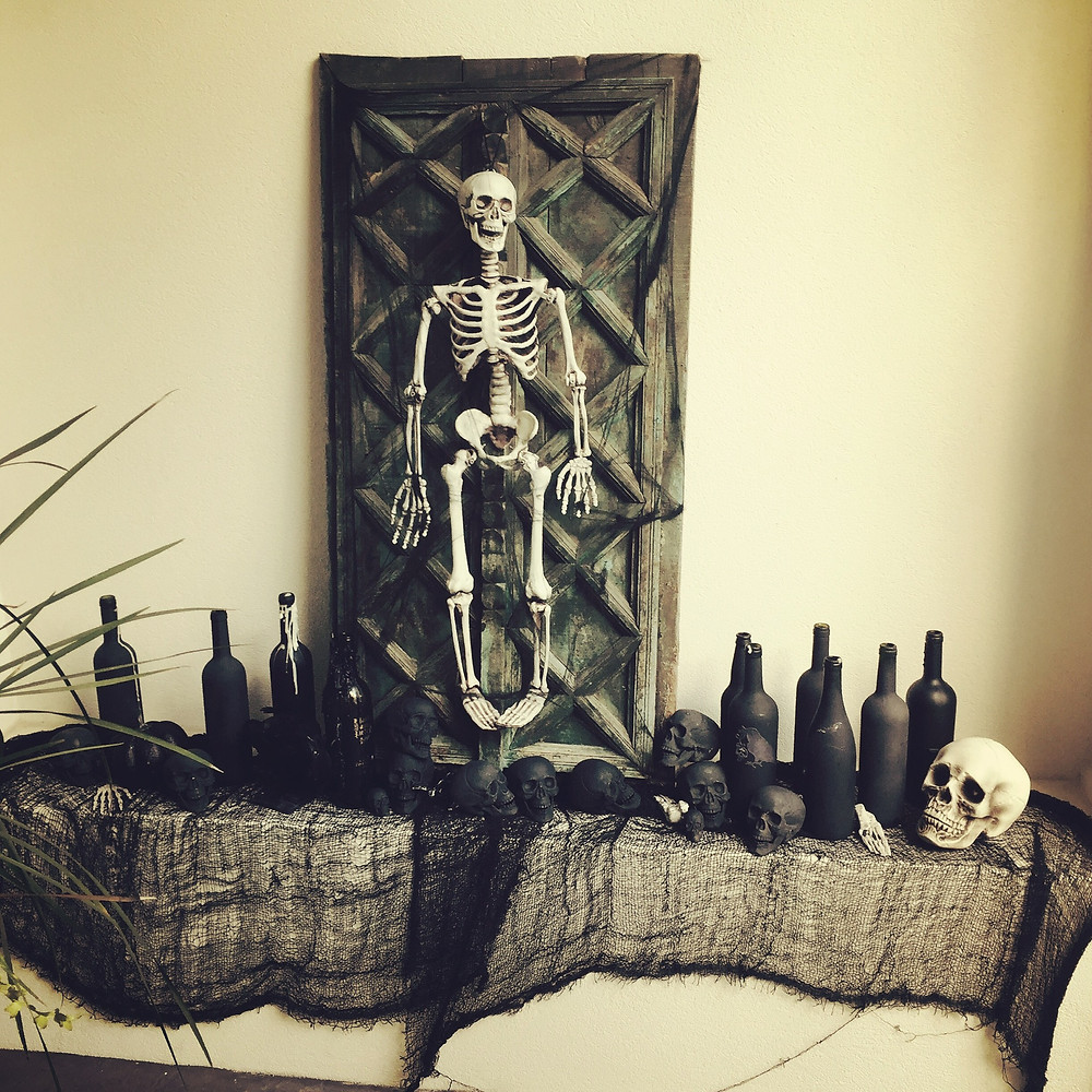Interior designer decorates for Halloween. Spooky and chic decorations. skeletons and black bottles on a niche